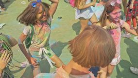 RÚSSIA, IRKUTSK - 27 DE JUNHO DE 2018: Jovens felizes que dançam e que comemoram durante o festival de Holi das cores Multidão de