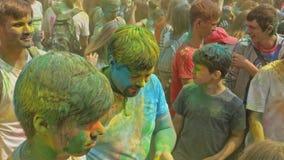 RÚSSIA, IRKUTSK - 27 DE JUNHO DE 2018: Jovens felizes que dançam e que comemoram durante o festival de Holi das cores Multidão de filme