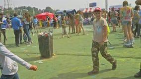 RÚSSIA, IRKUTSK - 27 DE JUNHO DE 2018: Jovens felizes que dançam e que comemoram durante o festival de Holi das cores Multidão de video estoque