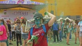 RÚSSIA, IRKUTSK - 27 DE JUNHO DE 2018: Jovens felizes que dançam e que comemoram durante o festival de Holi das cores Multidão de vídeos de arquivo