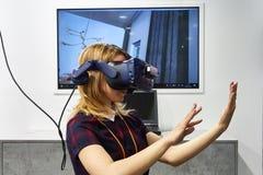 RÚSSIA, MOSCOU - ABRIL, 04, menina 2019 loura nova em auriculares aumentados da realidade imagens de stock royalty free