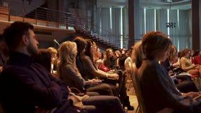 RÚSSIA, MOSCOU - 13 DE ABRIL DE 2019: Grande audiência fêmea que senta-se no salão na apresentação Arte Importante e informativo video estoque
