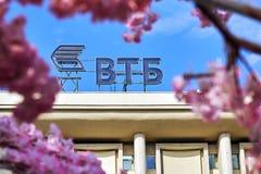 Rússia, Moscou - 30 de abril de 2018 Logotipo do banco de VTB visto através das flores de uma árvore de cereja decorativa na rua  Fotos de Stock Royalty Free