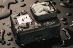 Rússia, Moscou - 3 de fevereiro de 2018: A câmera da ação do HERÓI 6 de GoPro na água deixa cair no fundo preto Corpo da câmera i Imagem de Stock
