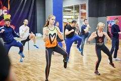 RÚSSIA, MOSCOU - 3 DE JUNHO DE 2017 grupo de pessoas que dá certo com os steppers no gym fotografia de stock royalty free
