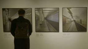 RÚSSIA, MOSCOU - 10 DE JUNHO DE 2017: Homem na sala da galeria que olha quadros de imagens Homem de negócios na vista da galeria  Fotos de Stock