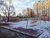 Rússia, Moscou, em março de 2019 Campo de jogos coberto pela neve manhã ensolarada Balanços e corrediças Mola adiantada Fundo da  foto de stock