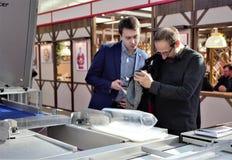 03 14 2019 Rússia, Moscou A padaria moderna Moscou da exposição, homens remove no telefone celular da câmera foto de stock