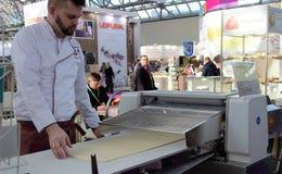 03 14 2019 Rússia, Moscou Padaria moderna Moscou da exposição o cozinheiro chefe rola a massa usando uma máquina da produção Foco fotografia de stock royalty free
