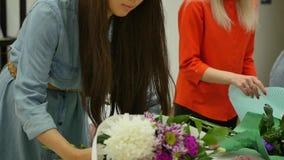 Rússia, Novosibirsk, em julho de 2019 As mulheres aprendem fazer o design floral sob a orientação de um profissional Um grupo de  video estoque