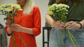 Rússia, Novosibirsk, em julho de 2019 As mulheres aprendem fazer o design floral sob a orientação de um profissional Um grupo de  filme