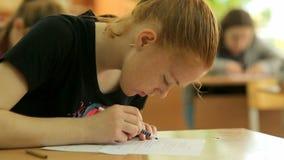 Rússia, Novosibirsk, 2015: Menina da escola em uma mesa da escola filme