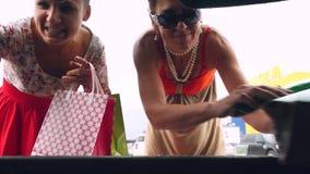 Rússia, Novosibirsk, o 28 de agosto de 2016 Mulheres felizes novas que põem sacos de compras no tronco de carro no shopping exter vídeos de arquivo