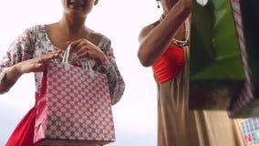 Rússia, Novosibirsk, o 28 de agosto de 2016 Mulheres felizes que põem sacos de compras no tronco de carro no shopping exterior Mu filme