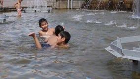 Rússia, Novosibirsk, o 10 de julho de 2016 Os meninos da empresa banham-se na fonte filme