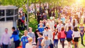 Rússia, Novosibirsk, 9 pode 2015 Multidão de povos que andam na rua em slowmotion Para mudar o foco do borrado filme