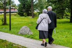 Rússia, Priozersk, em agosto de 2016: Um par idoso vai junto sob o braço na passagem de madeira fotografia de stock