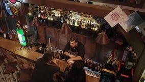 Rússia Rosa Khutor - em fevereiro de 2018: o empregado de bar comunica-se com um homem e uma mulher filme