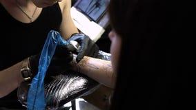 RÚSSIA, SAMARA - 21 DE SETEMBRO DE 2018: mãos do artista da tatuagem que criam uma tatuagem no braço de uma menina video estoque