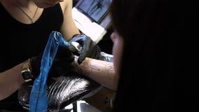 RÚSSIA, SAMARA - 21 DE SETEMBRO DE 2018: mãos do artista da tatuagem que criam uma tatuagem no braço de uma menina filme