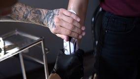 RÚSSIA, SAMARA - 21 DE SETEMBRO DE 2018: tatuagem provisória no braço do cliente que que faz o trabalhador no salão de beleza filme