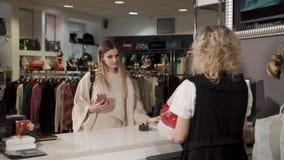 Rússia Togliatti - em dezembro de 2017: a mulher paga por compras, usando o smartphone filme