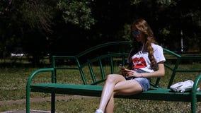 Rússia, Togliatty - 11 de julho de 2018: Menina bonita nova que escuta a música nos fones de ouvido, sentando-se em um banco filme