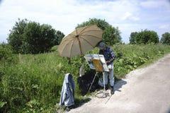 Rússia - Usolye o 16 de julho de 2017: pintor idoso com pinturas da escova à disposição na lona na natureza Imagens de Stock Royalty Free