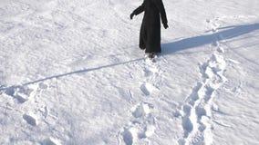 Rückmädchen des schusses A in einem schwarzen Mantel geht in die Schnee Spuren verschwinden stock footage