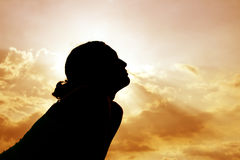 Rückseite beleuchtet vom Mädchen gegen Sonnenuntergang Lizenzfreies Stockbild