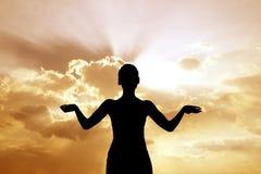 Rückseite beleuchtet von der Frau gegen Sonnenuntergang. Lizenzfreies Stockfoto