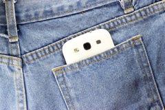 Rückseite Beschaffenheit von Blue Jeans mit Telefon Lizenzfreie Stockfotografie
