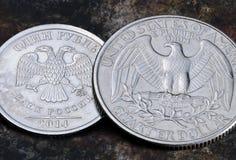Rückseite der einer Münze des russischen Rubels und fünfundzwanzig US-Cents Stockbild