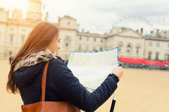 Rückseite der jungen Frau des Reisenden, die Richtung auf Karte sucht Lizenzfreie Stockfotografie