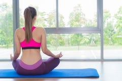 Rückseite des übenden Yoga der asiatischen Frau und Meditation in der Eignungsmitte stockfotografie