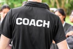 Rückseite des männlichen Sporttrainer tragenden TRAINER-Hemdes, sprechend mit seinem Team lizenzfreie stockfotografie