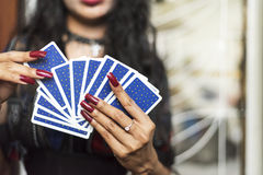 Rückseite ofTarot Karten in der Hand mit roten Nägeln stockbilder