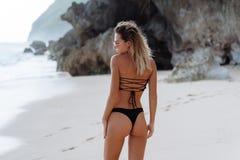 Rückseitenansicht des Mädchens mit Beute im schwarzen Bikini, der auf einsamem Strand stillsteht stockfotografie