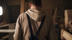Rückseitenansicht eines jungen Mannes in einem Sweatshirt und in einem blauen Overall, die eine Zimmereiwerkstatt durchlaufen möb stock video