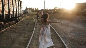Rückseitengesamtlänge der erschrockenen jungen Frau, die weg von einem Zombiemädchen durch Eisenbahn läuft Sun-Glanz auf dem Hint stock footage