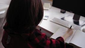 Rückseitengesamtlänge des unerkennbaren weiblichen Brunetteschreibens etwas auf Papier stock footage