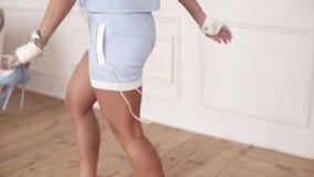 Rückseitengesamtlänge einer Frauenfigur mit gebräunter dem springendem Haut und stilvollen hellblauen Kostüm beim hohe Absätze he stock video