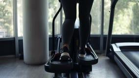 Rückseitengesamtlänge eines herrlichen athletischen Trainings der jungen Frau an der Turnhalle auf x-Trainer in den schwarzen Tur stock video
