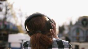 Rückseitengesamtlänge eines Mädchens mit einem braunen behaarten Endstück, das ein oover des karierten Hemds gegen die glänzende  stock video footage