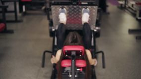 Rückseitengesamtlänge eines sportiven Brunettemädchens, das auf Beinpresse an der Turnhalle ausarbeitet Gesunder Lebensstil, Eign stock video footage