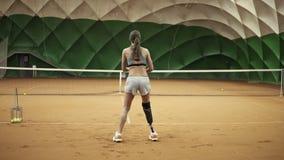 Rückseitengesamtlänge von zwei athletischen Mädchen, die Tennis in einem umfassten Tennisplatz spielen Frau im Rahmen mit einem B stock footage