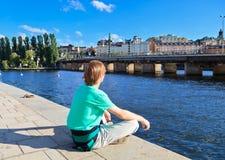 Rückseitige Ansicht des Mannes sitzend auf Pier Stockfotos