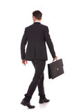 Rückseitige Ansicht eines gehenden Geschäftsmannes mit Aktenkoffer Lizenzfreies Stockfoto