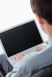 Rückseitige Ansicht eines Geschäftsmannes, der auf einem Laptop schreibt Lizenzfreies Stockfoto