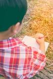 Rückseitige Ansicht Jungenschreiben auf Buch getrennte alte Bücher Abbildung der roten Lilie Lizenzfreies Stockfoto